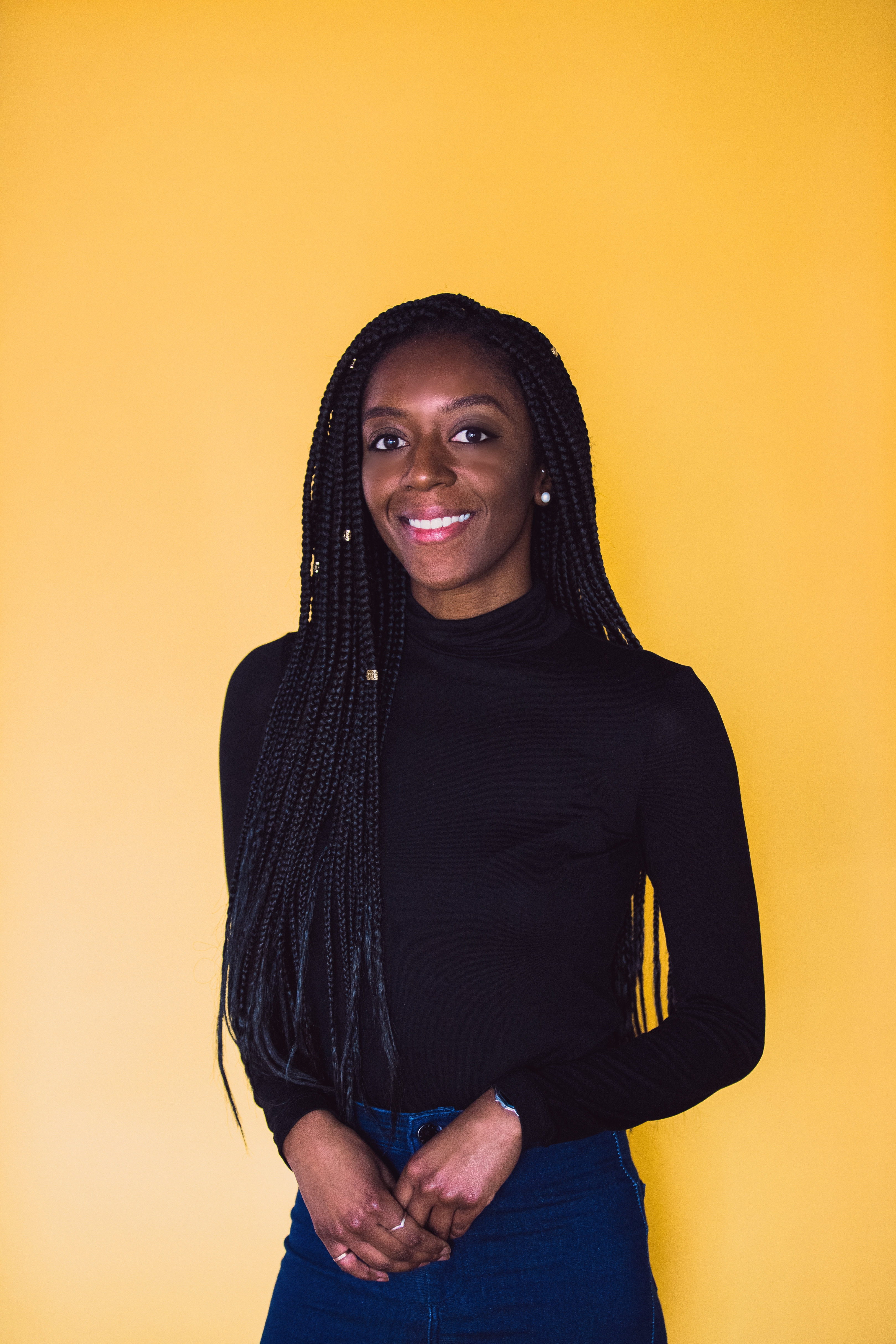 young girl (Afua Deborah) standing in front of yellow background